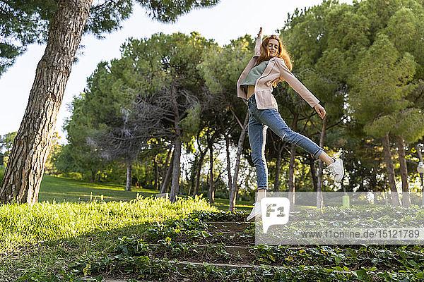 Junge rothaarige Frau springt in einem Park auf Treppen