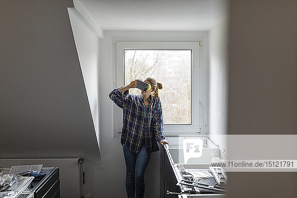 Young woman wearing VR glasses in unfinished kitchen