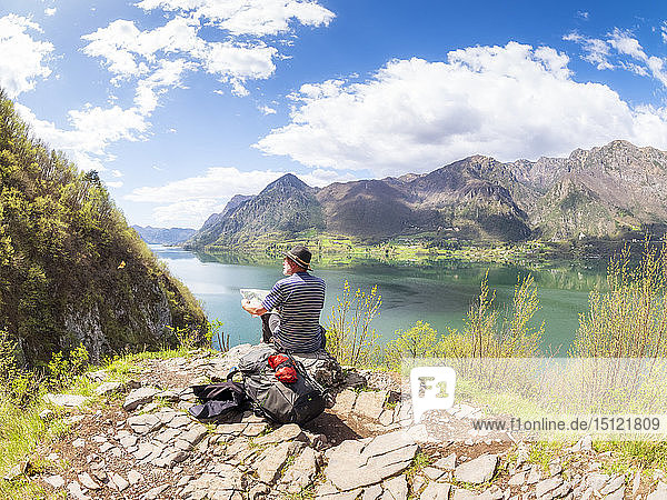 Italy  Lombardy  spring at Lake Idro  hiker sitting with map at observation point