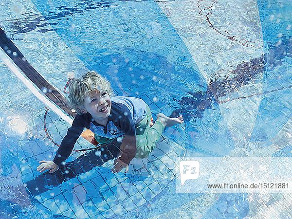 Porträt eines kleinen Jungen  der sich mit Bocciaball und Schwimmbad vergnügt
