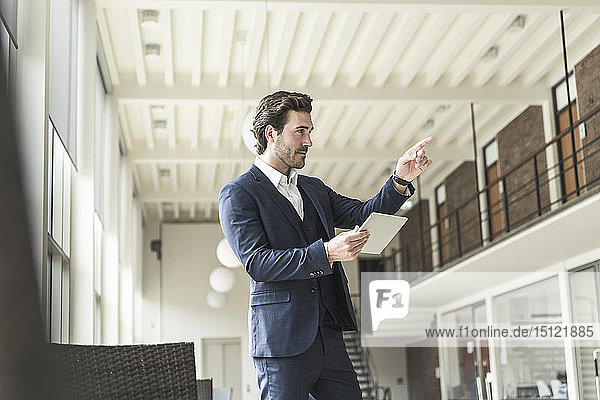 Successful manager standing in modern office building  using laptop  pointing