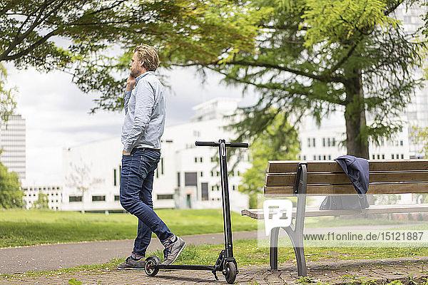 Geschäftsmann mit E-Scooter am Telefon im Stadtpark  Essen  Deutschland