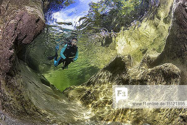 Österreich  Salzkammergut  Weissenbach  Taucherin in einem wilden Gebirgsfluss