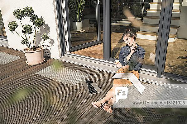 Junge Frau sitzt zu Hause auf der Terrasse und arbeitet mit Buch und Laptop