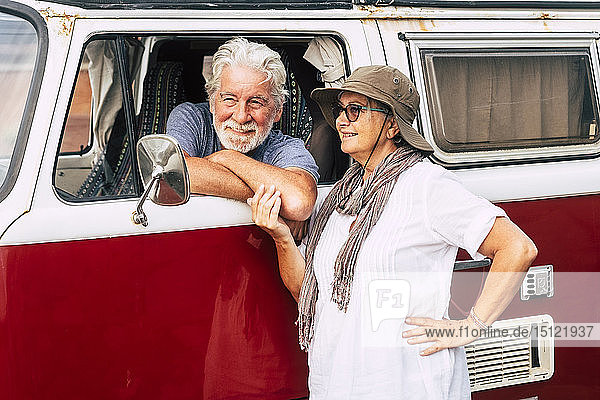 Senior couple traveling in a vintage van  taking a break at the sea  talking