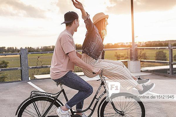 Glückliches junges Paar zusammen auf einem Fahrrad bei Sonnenuntergang auf dem Parkdeck