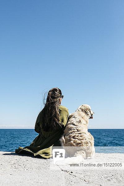 Rückenansicht einer Frau  die neben ihrem Labrador Retriever am Kai sitzt und auf das Meer schaut
