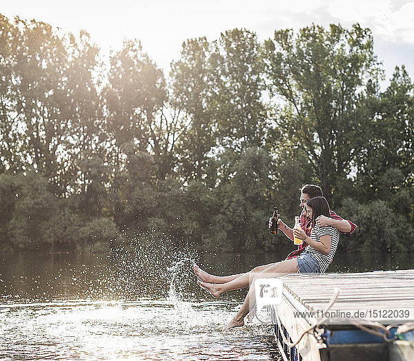 Glückliches junges Paar trinkt und planscht mit Wasser auf einem Steg an einem abgelegenen See