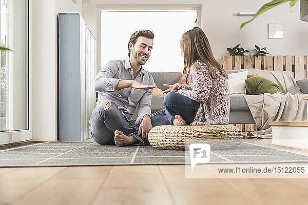 Junger Mann und kleines Mädchen sitzen zu Hause und spielen Papier  Schere  Stein