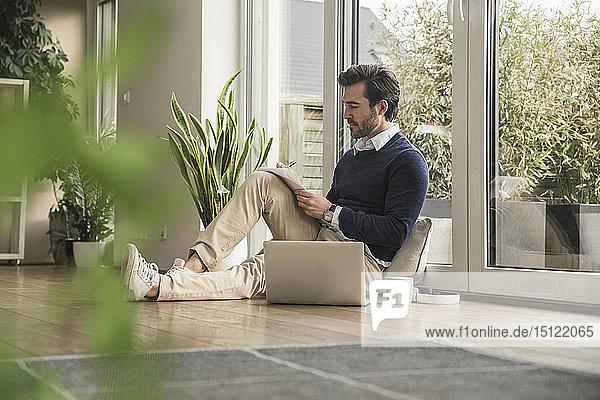 Junger Mann sitzt im Wohnzimmer  lehnt am Fenster  arbeitet mit dem Laptop  macht sich Notizen