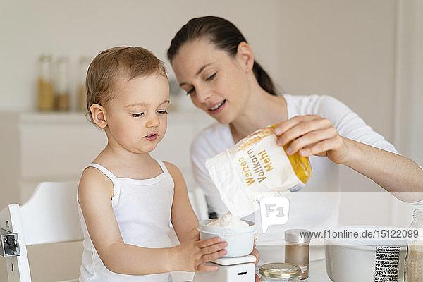 Mutter und kleine Tochter backen gemeinsam zu Hause in der Küche einen Kuchen und wiegen Mehl