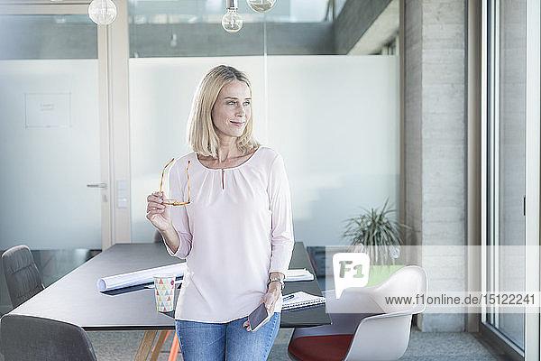Geschäftsfrau mit Brille und Handy im Büro mit Blick zur Seite