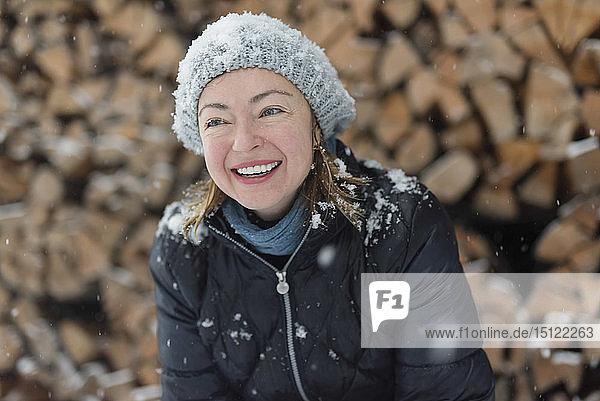Portrait of happy woman in snowfall