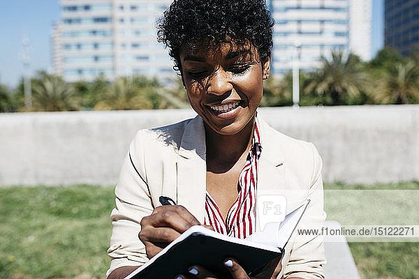 Frau schreibt Notizen in ein Notizbuch und sitzt auf einer Bank