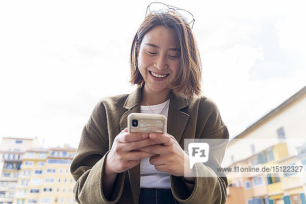 Italy,  Florence,  happy young woman using cell phone in the city
