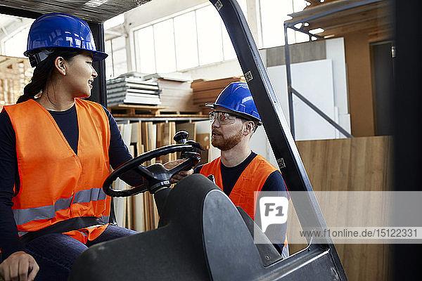 Mann spricht mit einer Arbeitnehmerin auf einem Gabelstapler in einer Fabrik