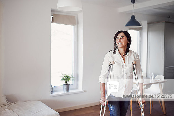 Mature woman with crutches  alone at home
