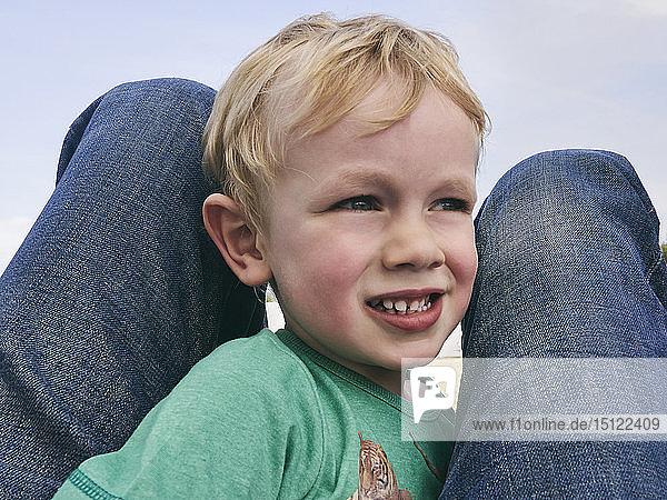 Porträt eines kleinen Jungen zwischen den Beinen seines Vaters  der in die Ferne schaut