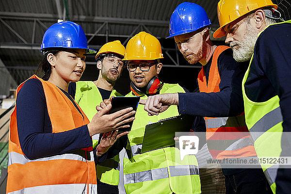 Arbeiter im Fabriklager sprechen und benutzen Tabletten