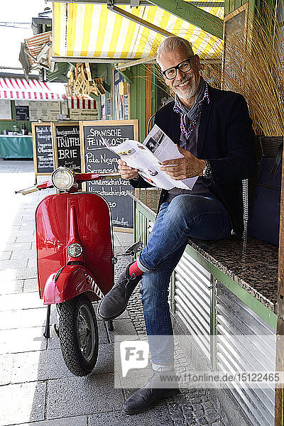 Mature man waiting at the market  reading brochure