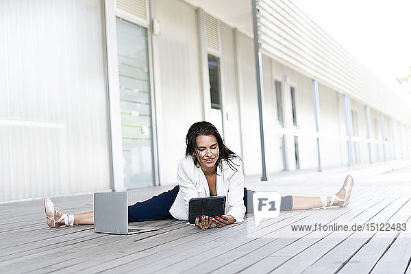 Baletttänzerin am Boden sitzend  mit Tablett und Laptop