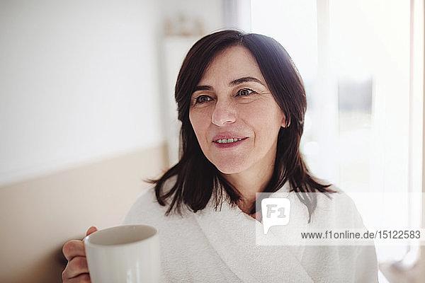 Reife Frau im Bademantel  die ihren Morgenkaffee trinkt