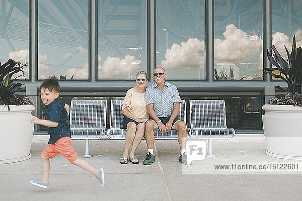 Großeltern schauen laufendem Jungen zu