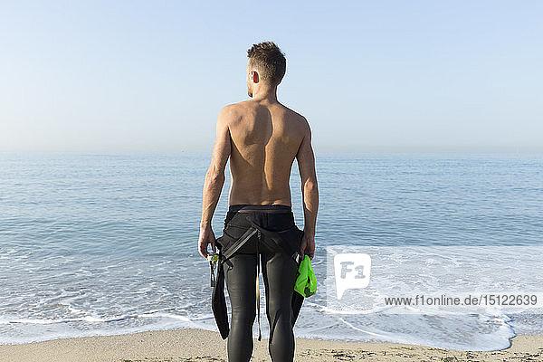 Rückansicht eines jungen Athleten am Strand  der sich auf das Schwimmen vorbereitet