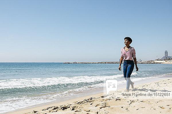 Woman walking on the beach  enjoying the sun after work