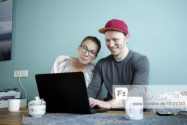 Mutter und Sohn sitzen am Küchentisch und benutzen einen Laptop