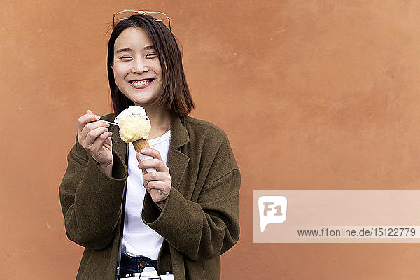 Happy young woman eating an ice cream cone at an orange wall