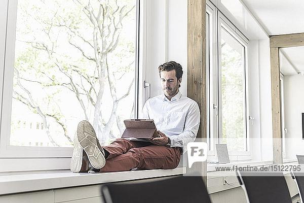 Junger Geschäftsmann sitzt auf der Fensterbank und benutzt ein digitales Tablett