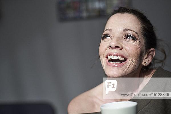 Lachende Frau mit Tasse zu Hause