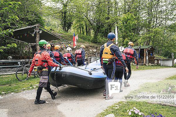 Eine Gruppe von Freunden bereitet sich mit einem Schlauchboot auf eine Rafting-Tour vor