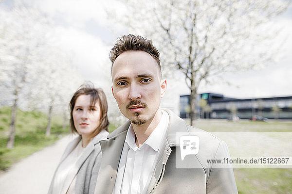 Porträt eines jungen Mannes mit Freundin im Hintergrund  in einem Park im Frühling