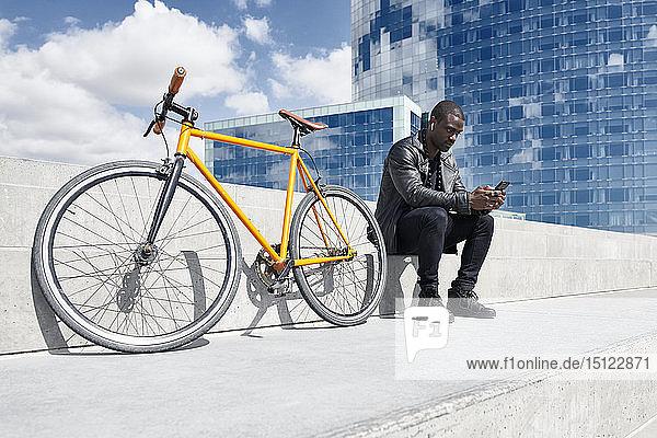 Mann mit gelbem Fahrrad sitzt auf einer Treppe und benutzt ein Smartphone  Barcelona  Spanien