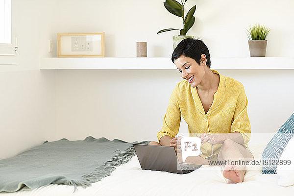 Lächelnde junge Frau mit Laptop im Bett