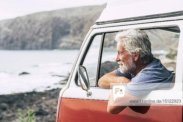 Älterer Mann reist in einem Kleinbus und schaut auf das Meer