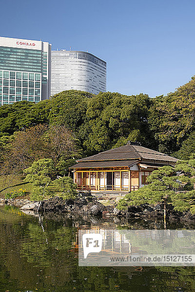 A modern highrise hotel above the Tsubame-no-ochaya  a tea house on a lake in the Hama-rikyu Gardens  Tokyo  Honshu  Japan  Asia