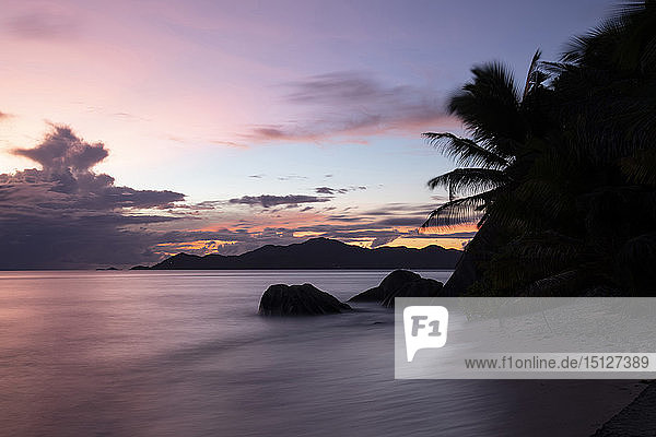 Sunset at Anse Source d'Argent looking toward Praslin  Union Estate Park  La Digue  Seychelles  Indian Ocean  Africa