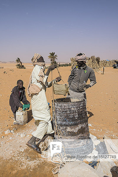 Local boys drawing water from their well in the desert between Ounianga Kebir and Faya  northern Chad  Africa