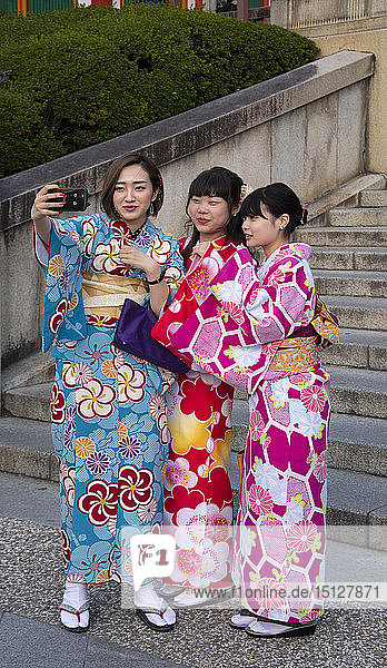 Young Japanese women dressed in colourful kimonos taking selfies in Kyoto  Japan  Asia