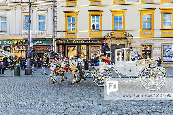 Horse drawn carriage in the main square  Rynek Glowny  in the medieval old town  UNESCO World Heritage Site  Krakow  Poland  Europe