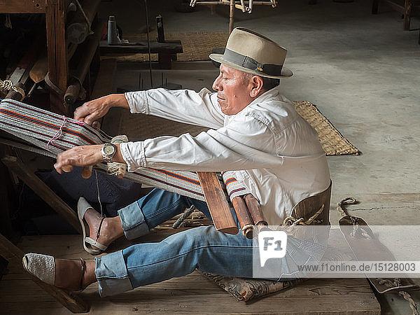 Indigenous man weaving with a backstrap loom  Otavalo  Ecuador  South America