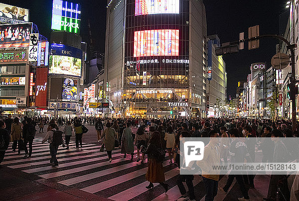 Neon signs above crowds at the Shibuya Crossing in Tokyo  Japan  Asia