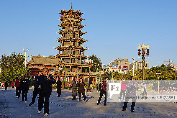Morning exercises in front of the wooden pagoda on the main square  Zhangye  Gansu Province  China  Asia