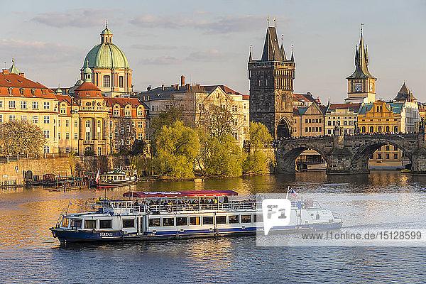 Tourist boat passing Charles Bridge and the Old Town Bridge Tower on Vltava River  Prague  Bohemia  Czech Republic  Europe