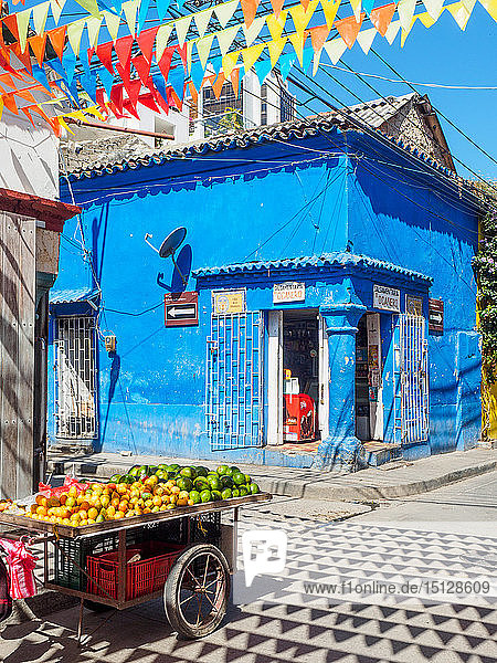 Colorful flags  blue building  and fruit cart on a street corner in Getsemani barrio  Cartagena  Colombia  South America