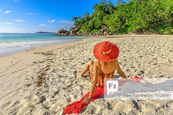 Tourist woman in red sun hat sitting on pristine white beach at sunset  Anse Georgette Beach  Praslin Island  Seychelles  Indian Ocean  Africa