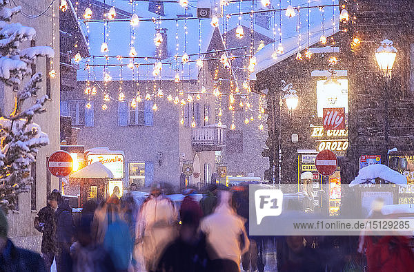 Busy street with tourists during snowfall  Livigno  Valtellina  Lombardy  Italy  Europe